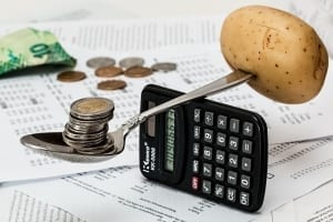 calculator balancing coins and potato